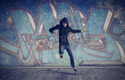 Póster Hombre joven que salta con un graffiti en el fondo