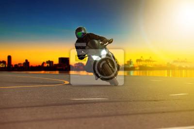 hombre montando motocicleta deportiva apoyándose en curva cerrada con fondo de escena de viaje