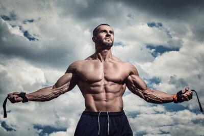 Póster Hombre musculoso bajo el cielo nublado