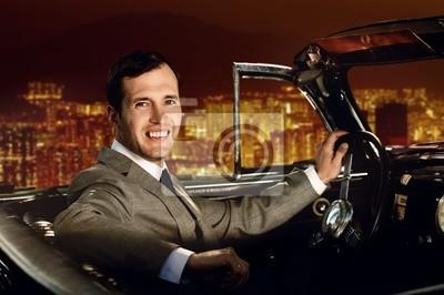 Hombre que conduce el coche retro contra la ciudad de noche