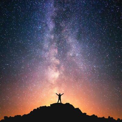 Póster Hombre y el Universo. Una persona que está de pie en la cima de la colina al lado de la Vía Láctea con sus manos levantadas al aire.