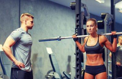 Póster Hombre y mujer con barbell flexionando los músculos en el gimnasio