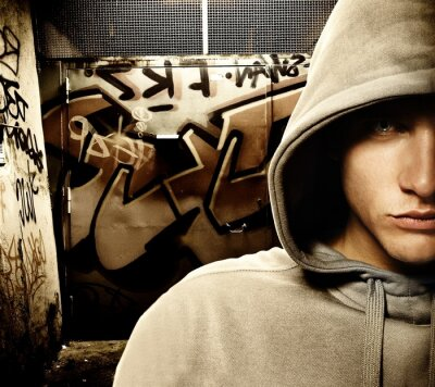 Hooligan de mirada fresco en un gateway de graffiti pintado