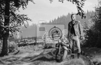 Joven apuesto motociclista de pie por su motocicleta crucero por encargo en un día soleado con bosque en el fondo y sonriente. Imagen horizontal. Efecto de desenfoque de la lente de cambio de inclinac