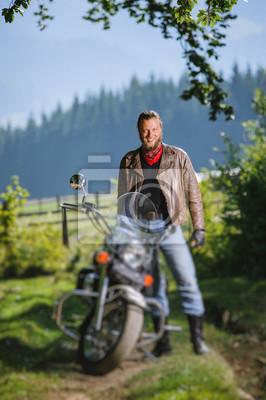 Joven apuesto motociclista de pie por su motocicleta crucero por encargo en un día soleado con bosque en el fondo y sonriente. Imagen vertical. Efecto de desenfoque de la lente de cambio de inclinació