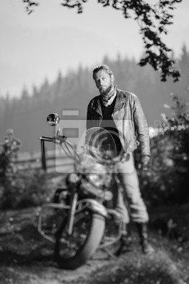 Joven apuesto motociclista de pie por su motocicleta de crucero por encargo en un día soleado con bosque en el fondo. Efecto de desenfoque de la lente de cambio de inclinación. En blanco y negro