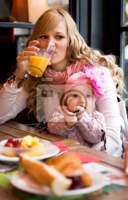 Joven madre y el bebé hija desayunando juntos en un Pa