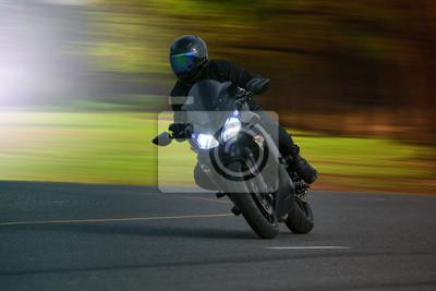 joven montado en motocicleta grande en bicicleta en el asfalto de alta manera contra