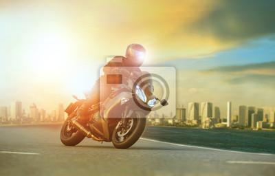 joven montando motocicleta grande apoyándose en curva cerrada con fondo de construcción urbana