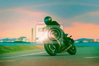 joven montando una motocicleta deportiva en las carreteras de asfalto contra la hermosa iluminación de la escena de la industria urbana, el uso como estilo de vida moderno y actividades de vacaciones