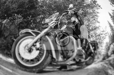 Joven motociclista con barba conducir su motocicleta crucero por carretera en el bosque. El hombre lleva chaqueta de cuero y vaqueros. Bajo punto de vista. Efecto de desenfoque de la lente de cambio d