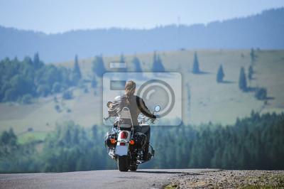 Joven motociclista con el pelo largo en el camino montañoso. El hombre está montando su moto de viaje hecho a medida en la carretera. Vista desde la parte posterior.