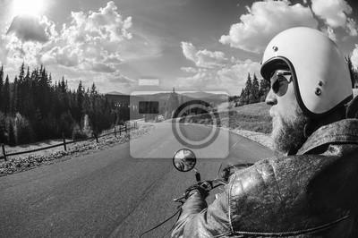 Joven motociclista conducir por el camino abierto en las montañas, vistiendo chaqueta de cuero y casco. Disparo desde la parte posterior. en blanco y negro