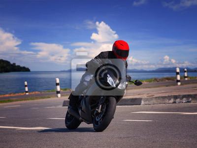 joven motociclista montando motocicleta en la carretera de asfalto contra beauti
