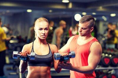 Póster Joven pareja con mancuernas flexión de los músculos en el gimnasio