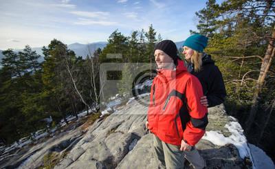 Joven pareja de excursionistas de pie en la cima de la montaña