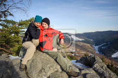 Joven pareja de excursionistas sentado en la cima de la montaña. Sonriendo y l