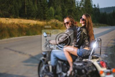 Joven pareja jinetes sentados juntos en brillante por encargo motocicleta crucero. Individuo y muchacha que llevan las chaquetas y las gafas de sol de cuero en un día asoleado. Vista lateral. Efecto d