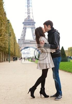 Joven pareja romántica besando a cerca de la Torre Eiffel en París