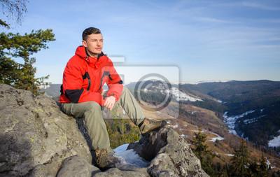 Joven turista sentado en la cima de la montaña y mirando en di
