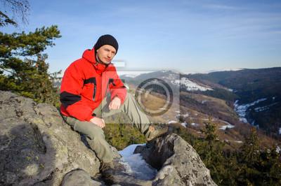 Joven turista sentado en la cima de la montaña y mirando hacia