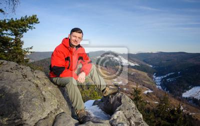 Joven turista sentado en la roca grande en la cima de la montaña