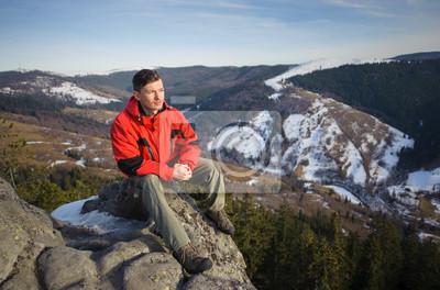 Joven turista sentado en la roca grande en la cima de la montaña y loo