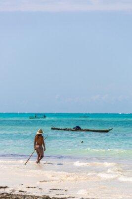 Joven vistiendo un sombrero de safari caminando en una playa tropical en Tanzania, África