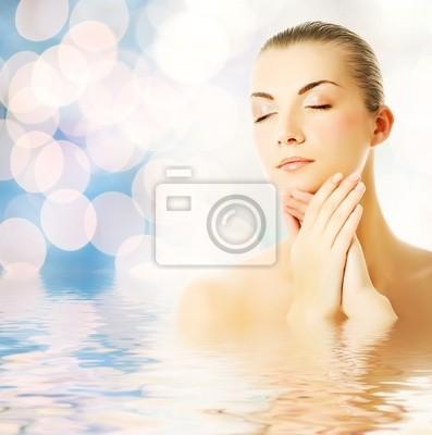 Joven y bella mujer en el agua masajear su cara