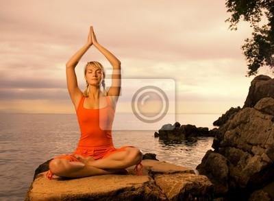 Joven y bella mujer haciendo ejercicio de yoga al aire libre