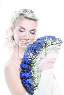 Joven y bella novia de lujo con ramo de rosas azules.