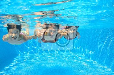 La familia feliz nadar bajo el agua en la piscina, que se divierten en vacaciones