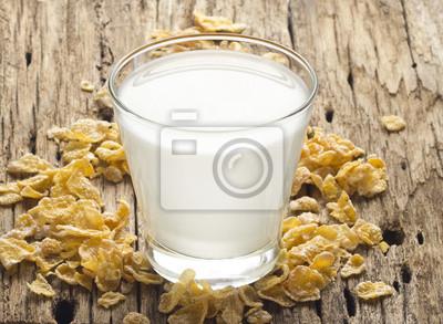 La leche fresca y copo de maíz en el fondo de madera vieja