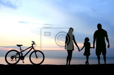 La madre y los niños siluetas en la playa al atardecer