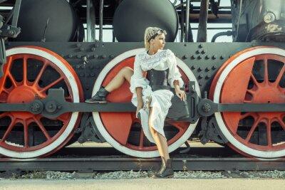 Póster La mujer en el vestido de la vendimia se está sentando en la rueda de la locomotora.
