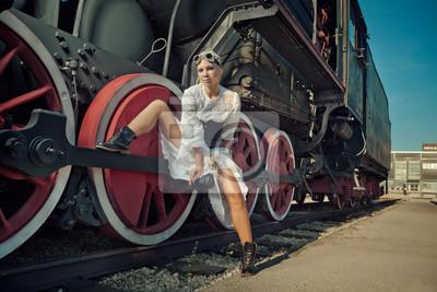 La mujer en el vestido de la vendimia se está sentando en la rueda de la locomotora.