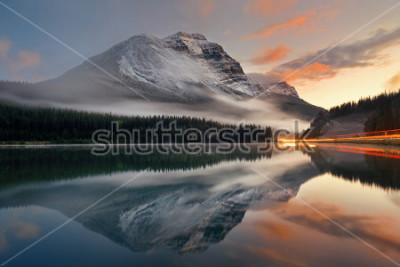 Póster Lago de la montaña y rastro del semáforo con la reflexión y niebla en la puesta del sol en el parque nacional de Banff, Canadá.