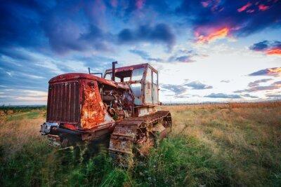 Póster Ld oxidado tractor en un campo en la puesta de sol