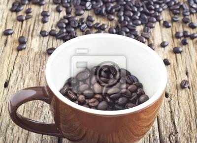 Los granos de café en la taza sobre la mesa de madera vieja