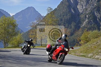 Los motociclistas en Plansee, montañas Ammer