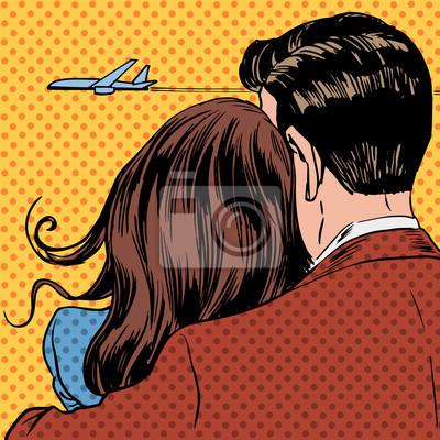 Los pares cariñosos mirando un avión que despegaba en el cielo