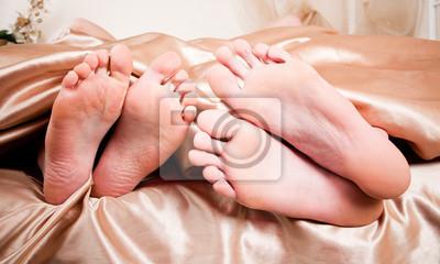 Los talones desnudos de par en palo de debajo de sábanas
