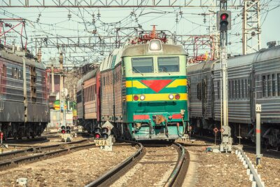 Póster Los trenes de pasajeros se mueven en la estación a la hora del día.