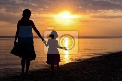 Madre e hijo en la playa de la puesta del sol
