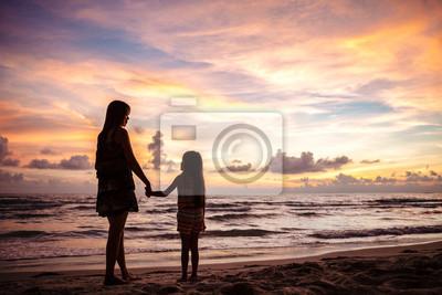 Madre y niño siluetas en la playa de la puesta del sol