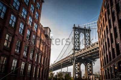 Póster Manhattan bridge seen from a narrow alley enclosed by two brick buildings on a sunny day in summer