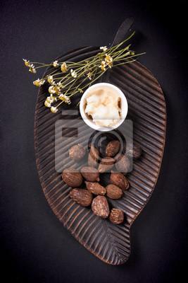 Mantequilla de karité y nueces de manteca de karité sobre fondo negro