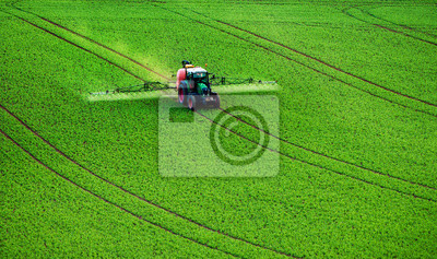 Maquinaria agrícola que rocía insecticida al campo verde, fondo agrícola natural de temporada de primavera