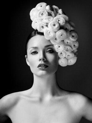 Póster modelo de moda con gran peinado y flores en el pelo.