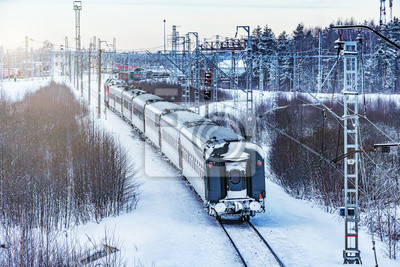 Modern high-speed train moves through the station at winter morning time. Fryazevo. Moscow region. Russia.